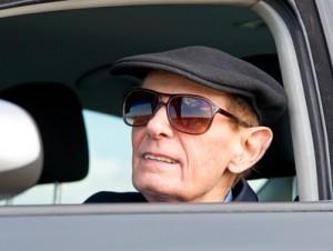 Ein alter Opa fährt gemütlich im Auto